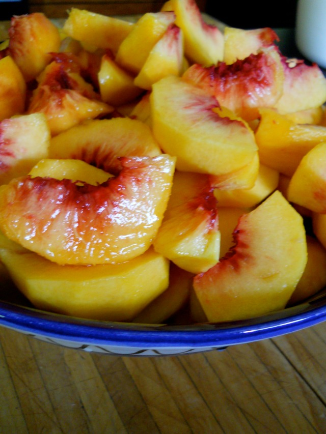 blue bowl of fresh slices of peaches